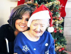 Felicia sits with Florence during a holiday party at an assisted living facility