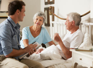 Home visit with a doctor, two elderly people in bed