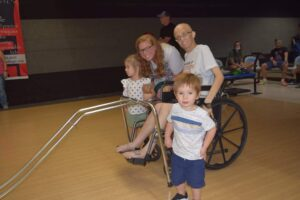 A man in a wheelchair poses with his wife and two small children at a bowling alley