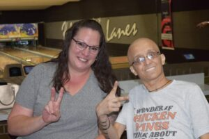 A man gives the peace sign alongside a caretaker at a bowling alley