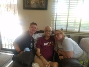 A couple pose with a hospice nurse in their home.
