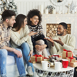 Multiethnic friends talking on Christmas morning at home, copy space
