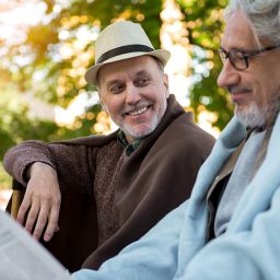 Portrait of happy male pensioner looking at his friend and smiling while he is reading paper